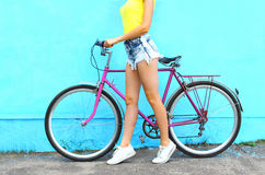 Fashion pretty woman and bicycle over colorful blue background Stock Photos