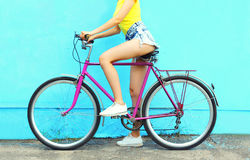Fashion pretty woman with bicycle over colorful blue background Royalty Free Stock Photos