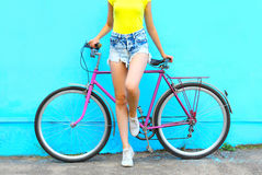Fashion pretty woman on bicycle posing over colorful blue Stock Image