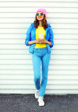 Fashion pretty woman with coffee cup in colorful clothes over white background wearing apink hat yellow sunglasses and blue jacket Royalty Free Stock Photos