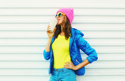 Fashion pretty woman with coffee cup in colorful clothes over white background wearing pink hat yellow sunglasses and blue jacket Royalty Free Stock Photo