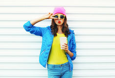 Fashion pretty woman with coffee cup in colorful clothes over white background wearing pink hat yellow sunglasses blue jacket Royalty Free Stock Photos