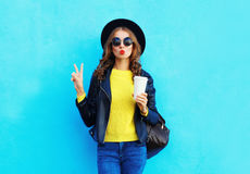 Fashion pretty woman with coffee cup wearing black rock style clothes over colorful blue. Background stock photography
