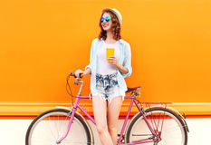 Fashion pretty woman with coffee or juice cup and retro vintage bicycle over colorful orange Stock Images
