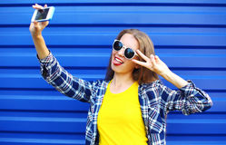 Fashion pretty woman in colorful clothes having fun makes self-portrait on the smartphone. Over blue background Stock Images
