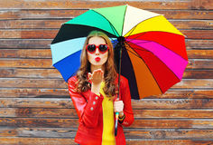 Fashion pretty woman with colorful umbrella sends air sweet kiss in autumn day over wooden background wearing red leather jacket Royalty Free Stock Images
