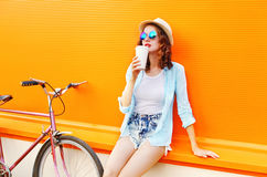 Fashion pretty woman drinks coffee from cup with bicycle over colorful orange Stock Photo