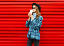 Fashion pretty woman drinks coffee from cup wearing a black hat coat jacket over colorful red Stock Images