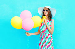 Fashion pretty woman drinks fruit juice from cup holds an air colorful balloons Stock Photos