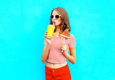 Fashion pretty woman drinks a fruit juice from a cup holds slice of watermelon ice cream. Over a colorful blue background Stock Photos