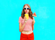 Fashion pretty woman drinks a fruit juice from cup holds slice of watermelon ice cream. Over a colorful blue background Stock Photo