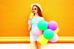 Fashion pretty woman drinks a fruit juice holds an air colorful balloons Stock Photo