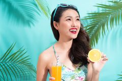 Fashion pretty woman drinks  juice from glass over colorful blue. Fashion pretty woman drinks juice from glass over colorful blue background Stock Images