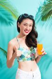 Fashion pretty woman drinks  juice from glass over colorful blue. Background Stock Images