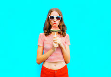 Fashion pretty woman is eating a slice of watermelon in the form of ice cream. A colorful blue background Royalty Free Stock Images