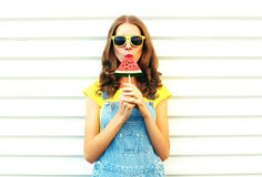 Fashion pretty woman eating a slice of watermelon in the form of ice cream on white background. Fashion pretty woman eating a slice of watermelon in the form of stock image