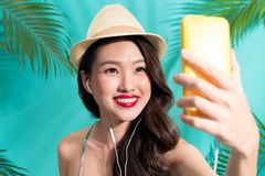 Fashion pretty woman with hat standing and taking selfie photo o. Ver colorful blue background Stock Photo
