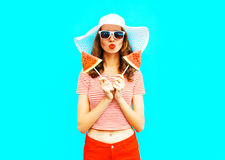 Fashion pretty woman is holding a two slices of watermelon in the form of ice cream. A colorful blue background Stock Photo