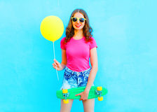 Fashion Pretty Woman Holds Yellow Air Balloon And Skateboard Having Fun Over Colorful Blue Stock Image
