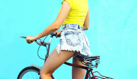 Fashion pretty woman in jeans shorts on bicycle over colorful blue background Royalty Free Stock Images