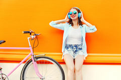 Fashion pretty woman listens to music in headphones near retro pink bicycle over colorful orange Royalty Free Stock Image