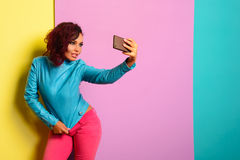 Fashion pretty woman makes self portrait on smartphone in blue jacket Stock Photo