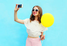 Fashion pretty woman makes self portrait on smartphone with yellow air balloon over colorful blue Royalty Free Stock Photos