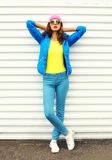 Fashion pretty woman model in colorful clothes posing over white background wearing pink hat yellow sunglasses and blue jacket Stock Photos