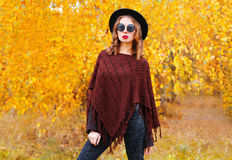 Fashion pretty woman model wearing a black hat, sunglasses and knitted poncho over autumn yellow leaves Stock Image