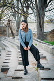 Fashion pretty woman model wearing a blue leather jacket. Posing over the stairs of abandoned stadium Royalty Free Stock Images