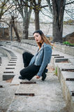 Fashion pretty woman model wearing a blue leather jacket. Sitting on the stairs of abandoned stadium Stock Image