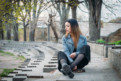 Fashion pretty woman model wearing a blue leather jacket. Sitting on the stairs of abandoned stadium Royalty Free Stock Image