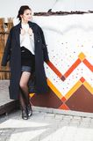 Fashion pretty woman model wearing a dark coat and white sweater posing over ethnic background stock photo