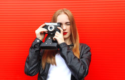 Fashion pretty woman with old retro camera over red Royalty Free Stock Photography