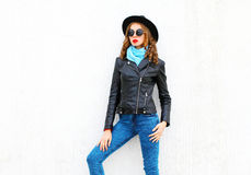 Fashion pretty woman posing wearing black rock jacket, hat over white. Background Stock Photos