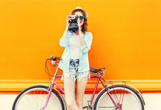 Fashion pretty woman with retro camera and bicycle over colorful orange stock photos