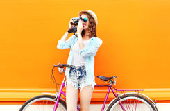 Fashion pretty woman with retro camera and bicycle over colorful orange background Royalty Free Stock Photography