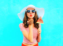 Fashion pretty woman sends an air kiss blowing red lips with a slice of watermelon ice cream Stock Image