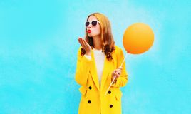 Fashion pretty woman sends an air kiss holds balloon in a yellow coat Royalty Free Stock Image