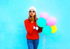 Fashion pretty woman sends an air kiss holds a balloons. On blue background Royalty Free Stock Photos