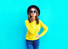 Fashion pretty woman sends air sweet kiss wearing a black hat and yellow knitted sweater over colorful blue. Background Royalty Free Stock Photography