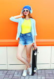 Fashion pretty woman with a skateboard in the city over orange colorful royalty free stock image