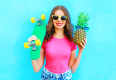 Fashion pretty woman with skateboard and pineapple sunglasses having fun over colorful blue. Background Stock Images