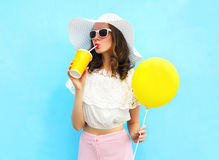 Fashion pretty woman in straw hat with air balloon drinks fruit juice from cup over colorful blue