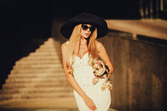 Fashion pretty woman in summer hat. Fashion portrait pretty woman in summer hat and Yorkshire Terrier in hand Stock Images