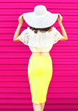 Fashion pretty woman in summer straw hat skirt over colorful pink Royalty Free Stock Image