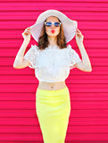 Fashion pretty woman in summer straw hat and skirt over colorful pink Royalty Free Stock Photography