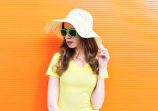 Fashion pretty woman in sunglasses and straw hat over colorful. Background Royalty Free Stock Photo