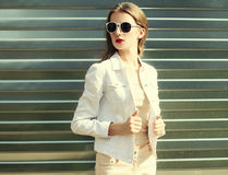 Fashion pretty woman in sunglasses and white denim jacket Royalty Free Stock Photography