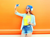 Fashion pretty woman is taking a picture self portrait on a smartphone over colorful orange. Background Stock Image